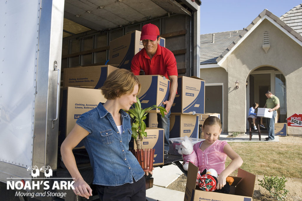 Family and worker unloading truck of cardboard boxes